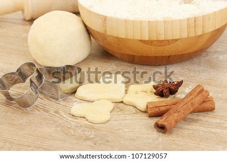 Cookie cutter with rolling pin on wooden table close-up