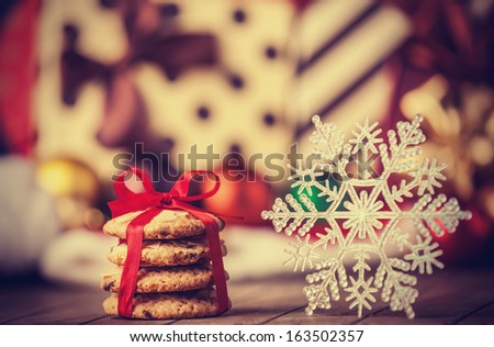 Cookies and snowflake with christmas gifts on wooden table