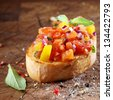 Cooking colourful bruschetta with toasted crispy sliced baguette topped with chopped tomato, onion, oil, seasoning and fresh basil on an old wooden table with scattered remnants of ingredients - stock photo