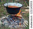 Cooking goulash in a kettle on a fire - stock photo