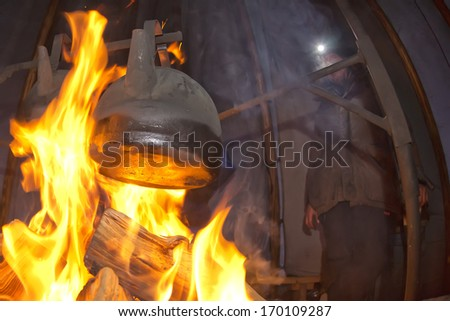 cooking on the campfire inside a tent in winter time