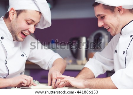 Cooking process concept. Smiling cooks in uniform putting filler of spinach and soft feta cheese on slice of puff pastry and making french chausson. Close up. Indoor shot