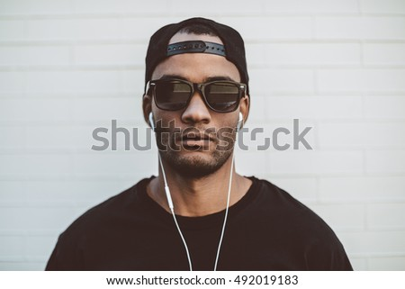 Cool and handsome. Handsome young African man in headphones looking away and looking serious while standing in front of the stoned wall outdoors
