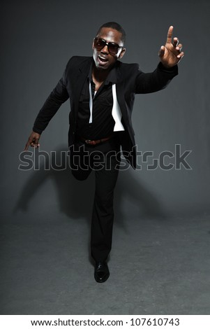 Cool black american man in dark suit. Studio fashion shot isolated on grey background. Wearing dark sunglasses.