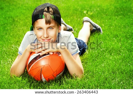 Cool boy lying on a grass with a football at a park. Summer day.