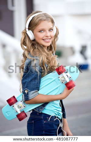 Cool girl with headphones and skateboard in city. Healthy, beautiful smile, the child to the dentist.Portrait of a little girl with orthodontic appliance.
