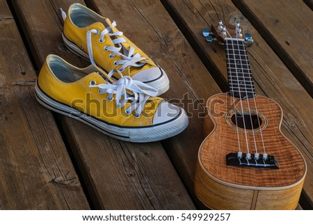 Cool teenager yellow sneakers hawaiian guitar on wooden background