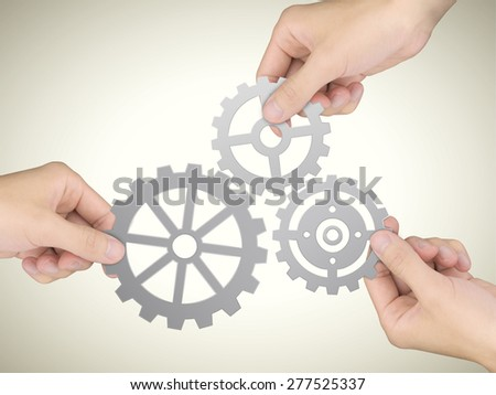 cooperation concept: hands holding gears over beige background