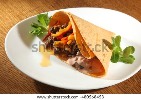 corn tortilla with meat and peppers on plate