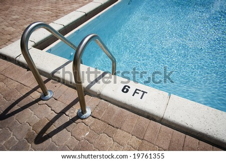 Corner of a swimming pool with stairs.
