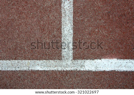 Corner of running track with white striped on redbrick color background.