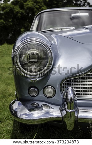 CORNWALL, UK - CIRCA JULY 2015: Classic Aston Martin DB5 blue metallic silver chrome front view of the car taken from a low angle. Vertical. Focus on headlight.