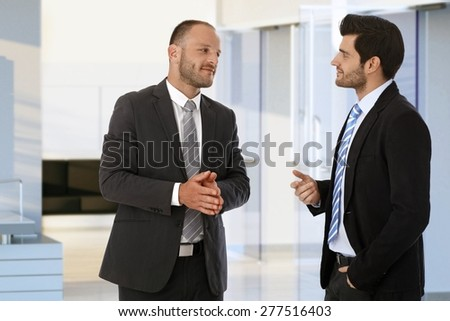 Corporate businessmen meeting and talking on office corridor.