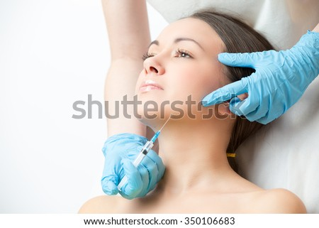correcting injection in the chin of young woman face