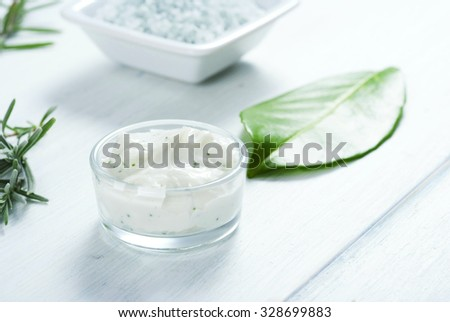 cosmetic cream and bath salt on white wooden table