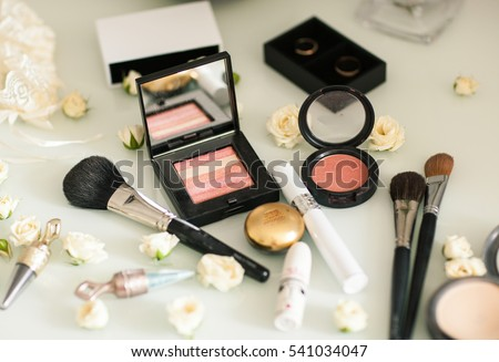 Cosmetics with eye shadow, eye liner and powder on white table