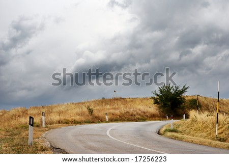 Country road curve in dark stormy weather