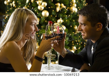 Couple at restaurant on dinner party. They're looking at each other and raise a toast.