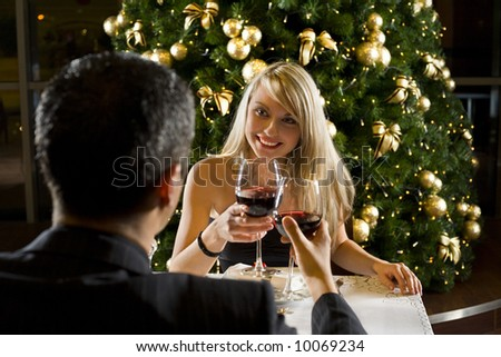 Couple at restaurant on dinner party. They're looking at each other and raise a toast. Focused on her.