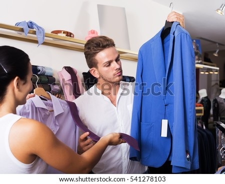 Couple choosing shirt, jacket and necktie at clothing shop