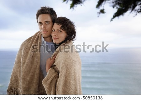 Couple covered by blanket standing by sea, portrait