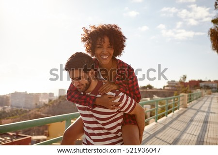 Couple doing the piggy back ride with her on his back, right arm around his neck, left hand on his shoulder and toothy smile