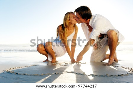 Couple draw a heart in the sand and share a romantic kiss on the beach in summer