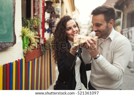 Couple eating pizza outdoors and smiling