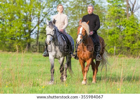 Couple enjoy riding horses in summer meadow.