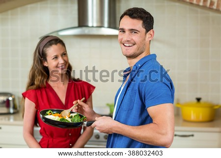 Couple holding pan of vegetables and smiling at each other in kitchen