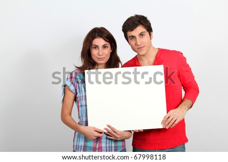 Couple holding whiteboard with happy look