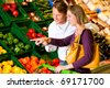 Couple in a supermarket at the vegetable shelf shopping for groceries, they are checking out the groceries - stock photo
