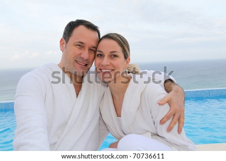 Couple in bathrobe sitting by swimming-pool