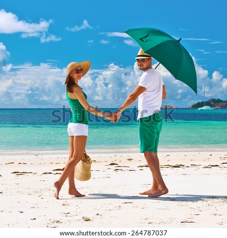 Couple in green with umbrella on a tropical beach at Seychelles