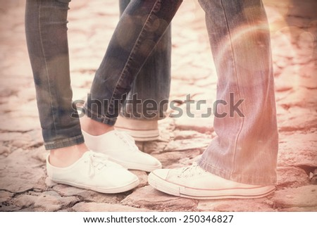 Couple in jeans standing on path on a sunny day in the city