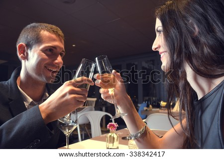 couple in love having dinner at a romantic restaurant and toasting with champagne