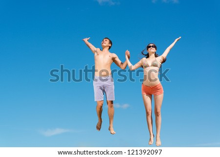 couple jumping together holding hands on a background of blue sky