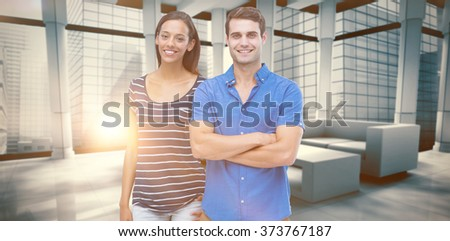 Couple looking at camera against modern room overlooking city