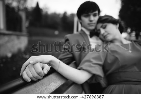 Couple lying on the bench. Close up hand in hand of couple. Black and white photo