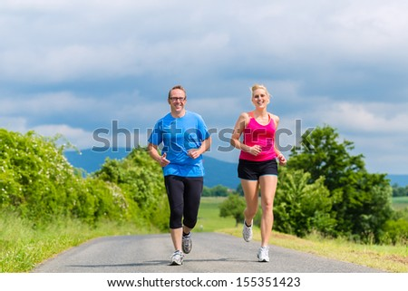 Couple, man and woman doing jogging or outdoor sport for fitness on rural street