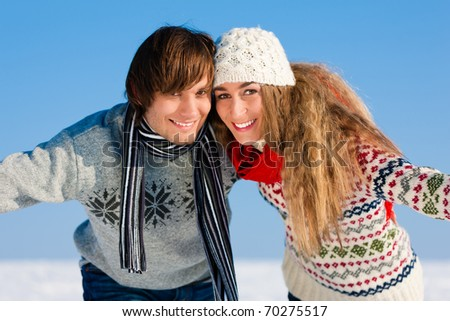 Couple - man and woman - having a winter walk embracing each other