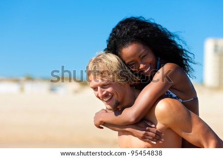 couple - man and woman - on the beach having lots of fun, the man is carrying the woman pack back