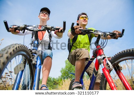 Couple of cyclists riding bicycles in park