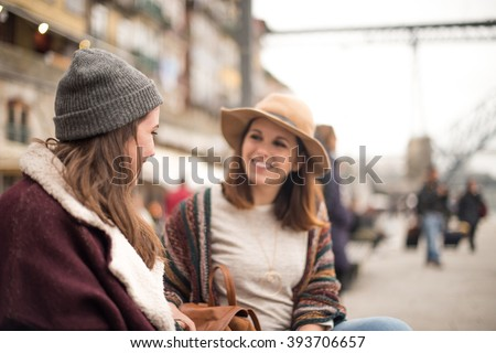 Couple of friends talking in the city with winter clothes