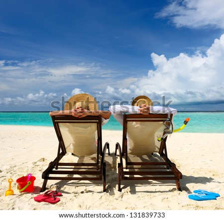 Happy couple sitting on colorful adirondack stock photo for Tropical vacations for couples