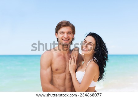 Couple on beach summer vacation, beautiful young happy couple love smiling embracing, man and woman smile over sea blue sky, concept ocean holiday travel