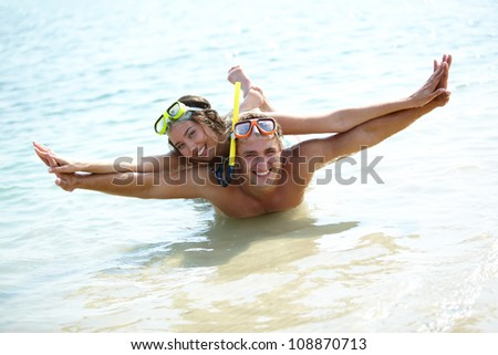 Couple playing in shallow water holding hands as if flying