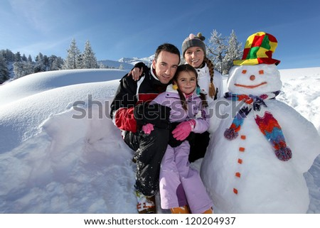 couple posing with child beside snowman at mountain resort