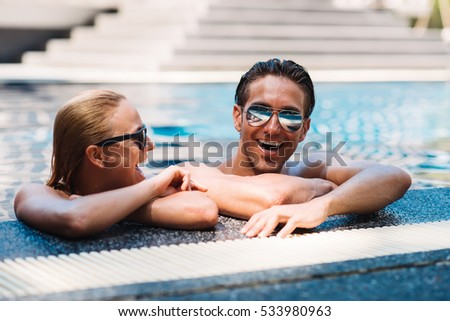 Couple relaxing in  swimming-pool
