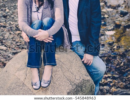 Couple sitting and leaning on rock in river bed.